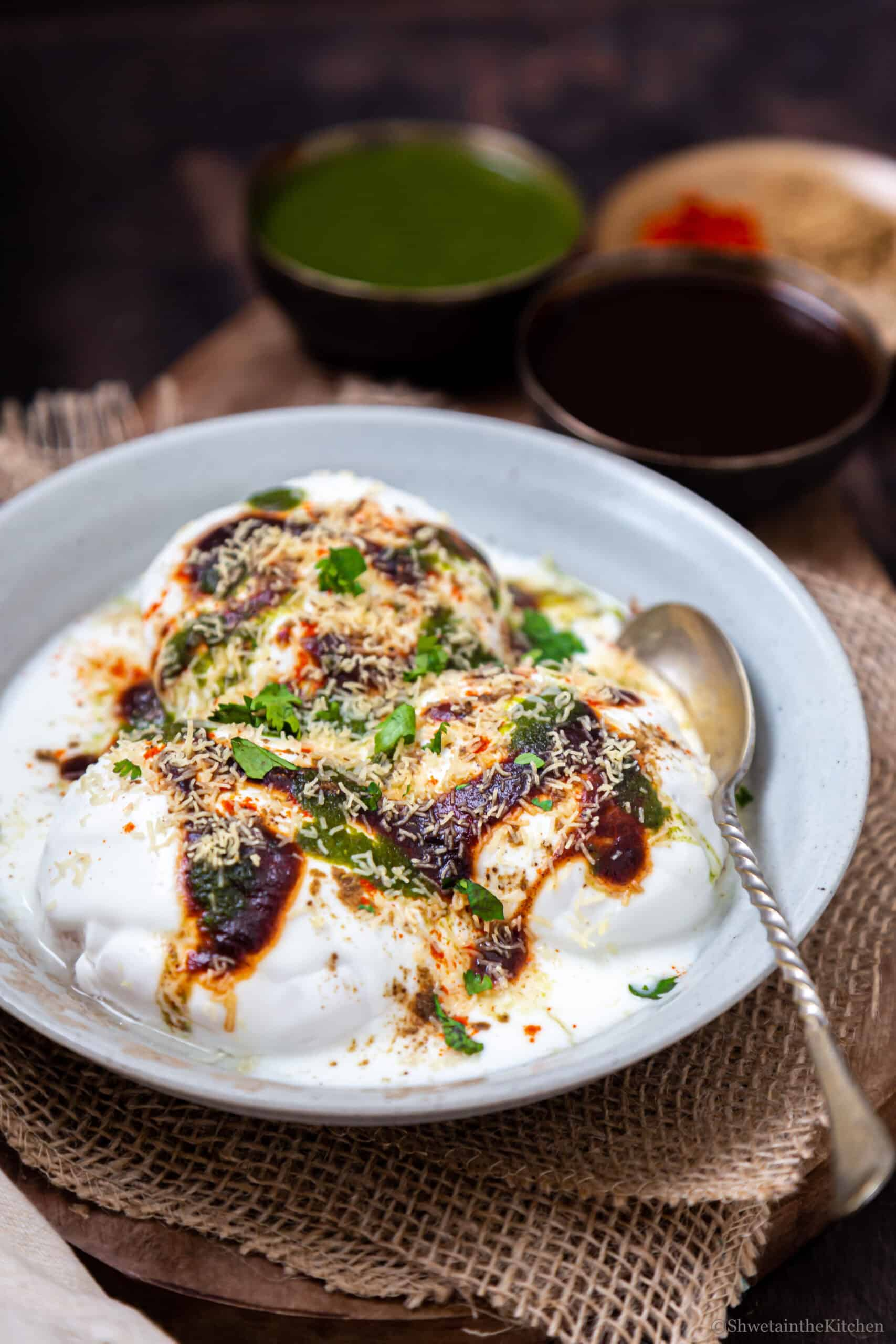 side view of Dahi Vada (Dahi Bhalla) served on a white plate with sweet and spicy chutneys.