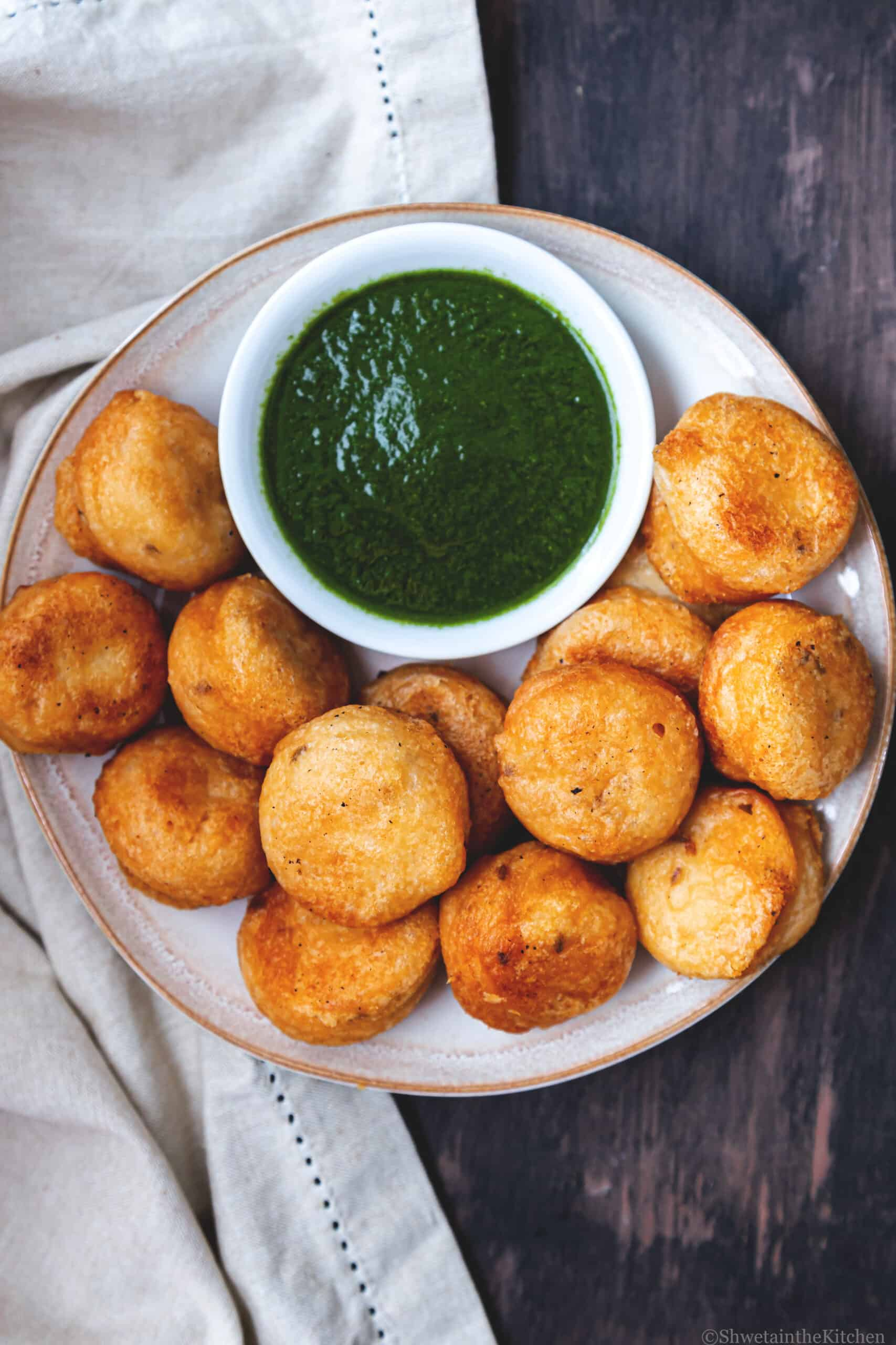 Plate with plain Vada (medhu wada) and bowl of green chutney