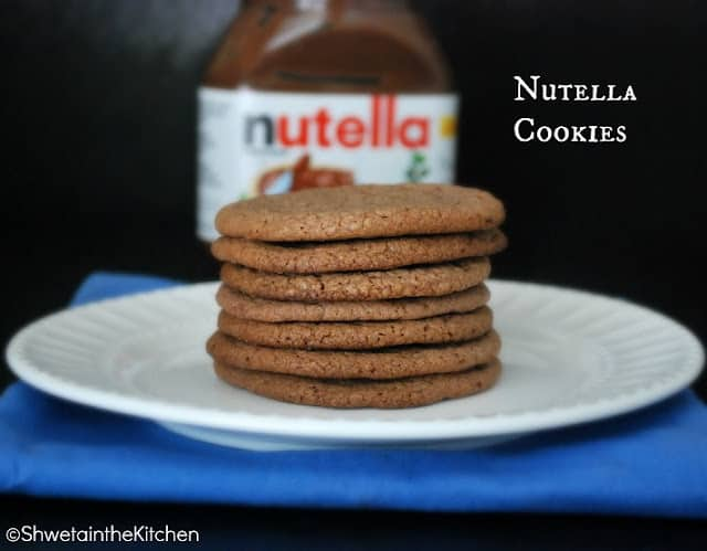 Seven nutella cookies stacked on top of each other on a white plate.