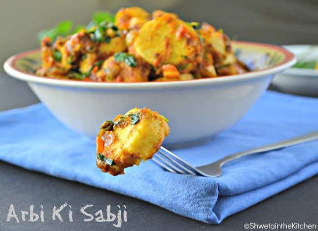 Arbi ki sabji on a fork in front of a bowl