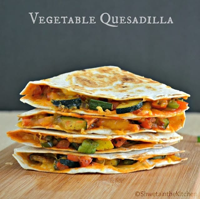 Vegetable quesadillas stacked on top of eachother on a wooden chopping board
