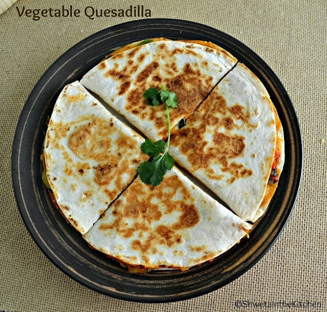 Overhead shots of quesadillas on a plate cut and garnished with fresh herbs