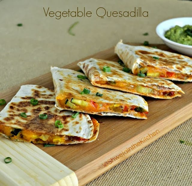 Vegetable quesadillas served on a wooden board with a guacamole dip