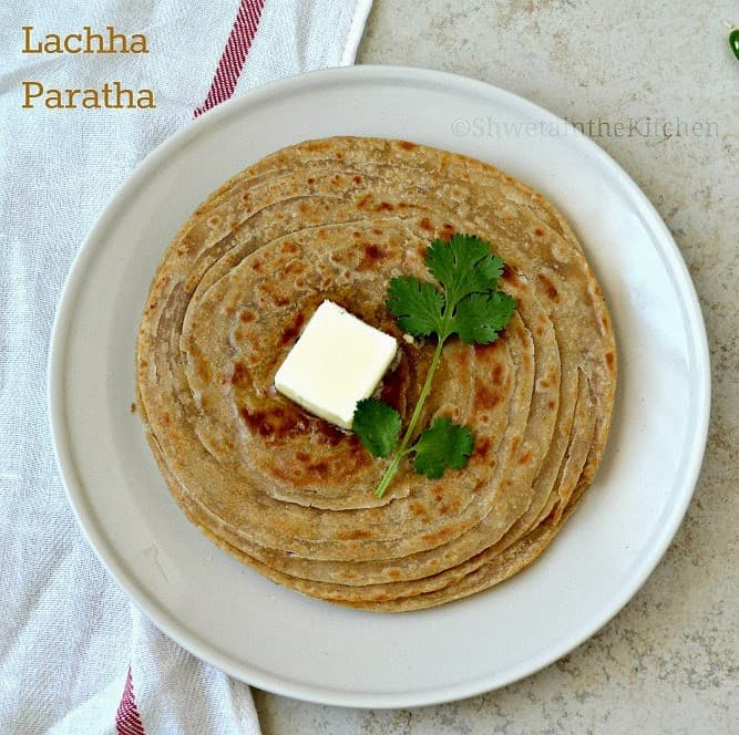 Lachha paratha served on a white plate with butter and fresh herbs