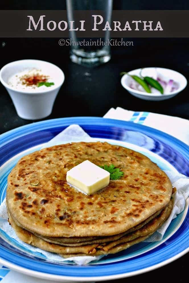A stack of mooli paratha served on a plate and topped with a pat of butter.