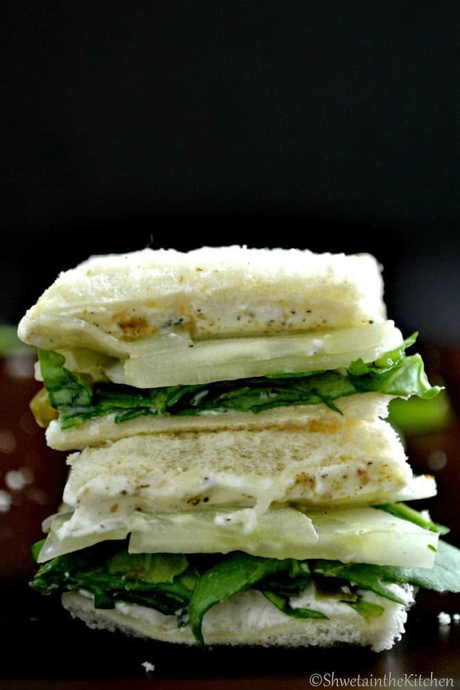 Cream cheese cucumber sandwiches stacked on top of eachother