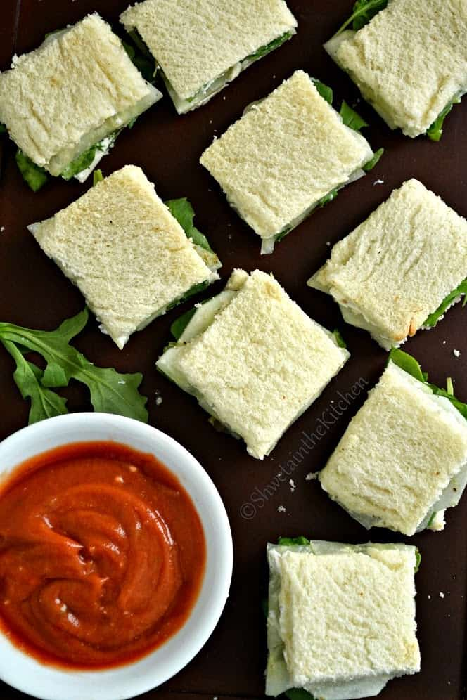 Sandwiches cut into squares served with a red dip