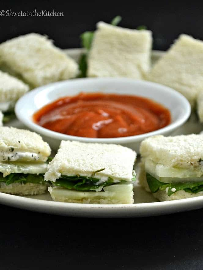 Sandwiches cut into squares and arranged around a red sauce on a silver serving plate
