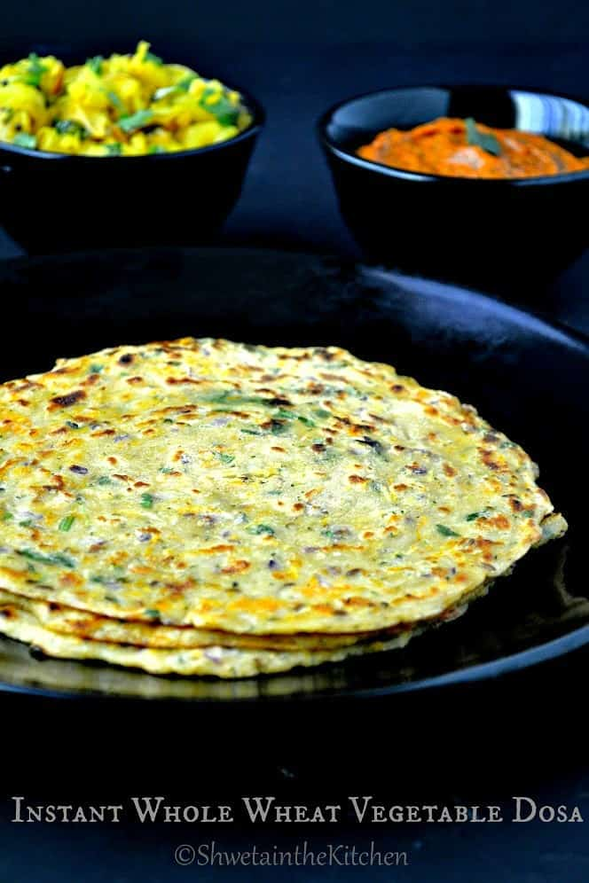 Three vegetable dosas stacked on a black plate in front of bowls of chutney