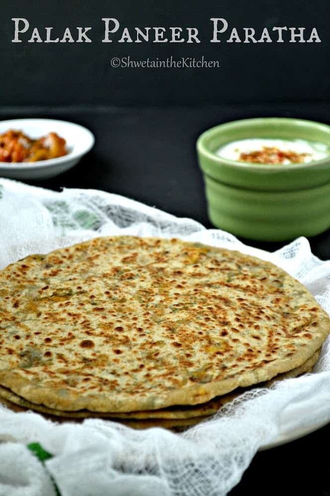 Stuffed parathas served on top of each other next to dips