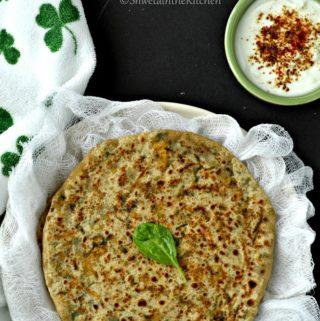 Palak paneer paratha garnished with some fresh herbs