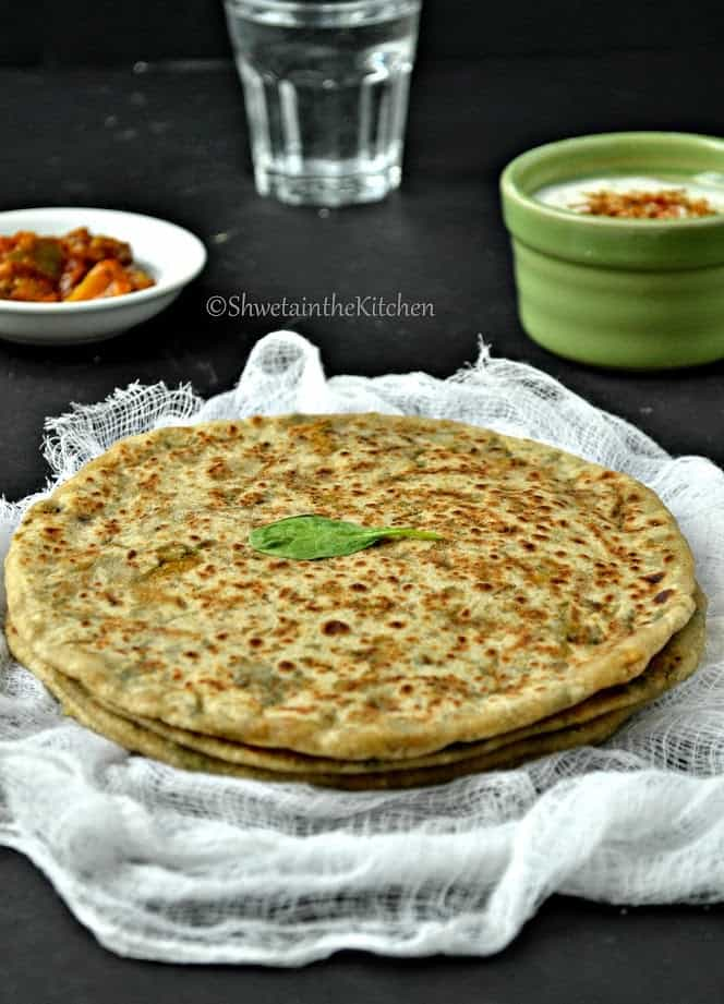 Palak panner paratha served with dips and garnished with a fresh herb