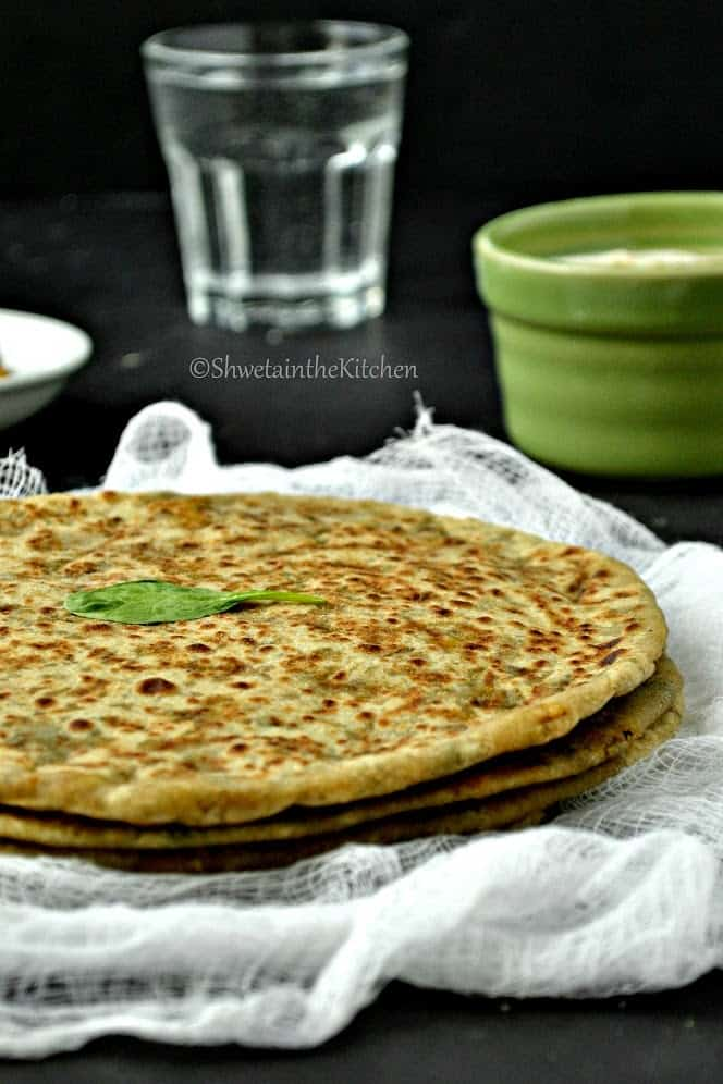Close up of palak panner paratha stacked on top of eachother on a piece of white cloth