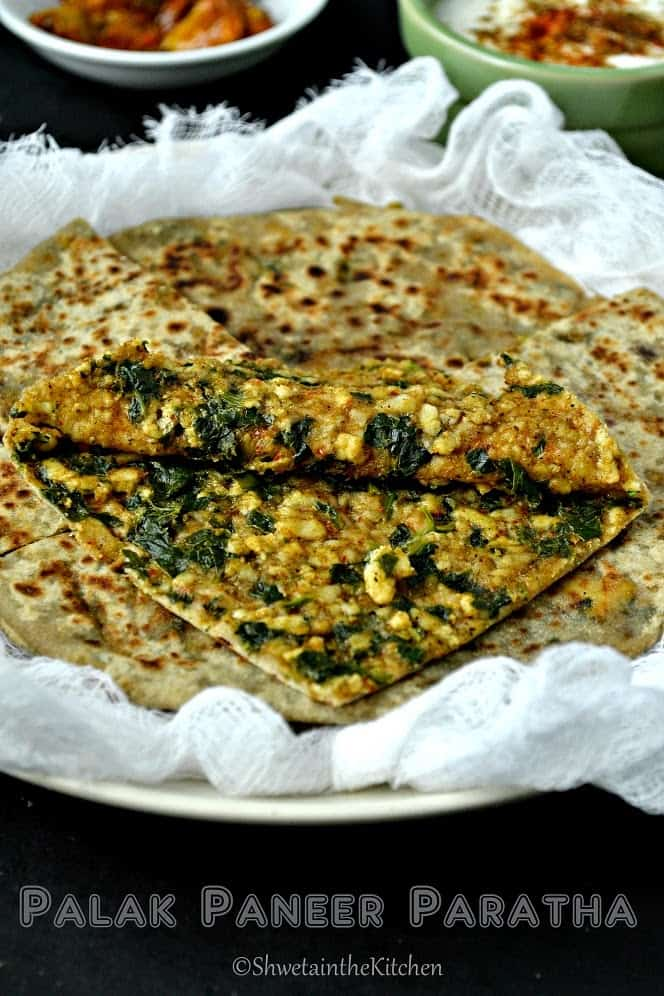 The top of a paratha folded over so that you can see the spinach and paneer filling