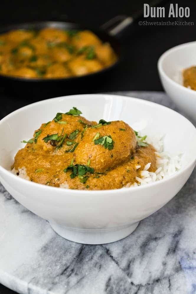 Dum aloo served in a white bowl over boiled rice