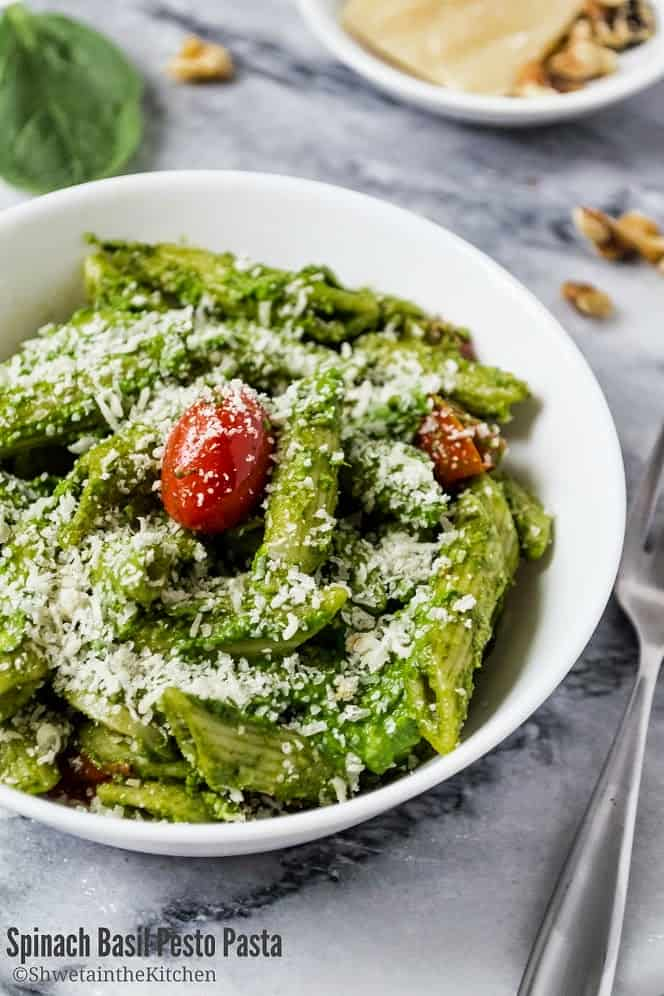 Bowl of spinach pesto pasta with tomato at centre