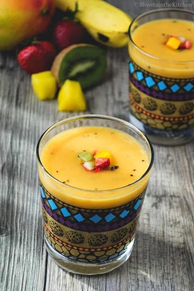 A tropical smoothie next to fresh fruits