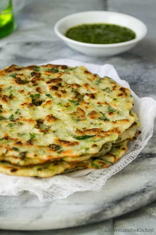 Cucumber thalipeeths stacked on top of each other in front of a green chutney.