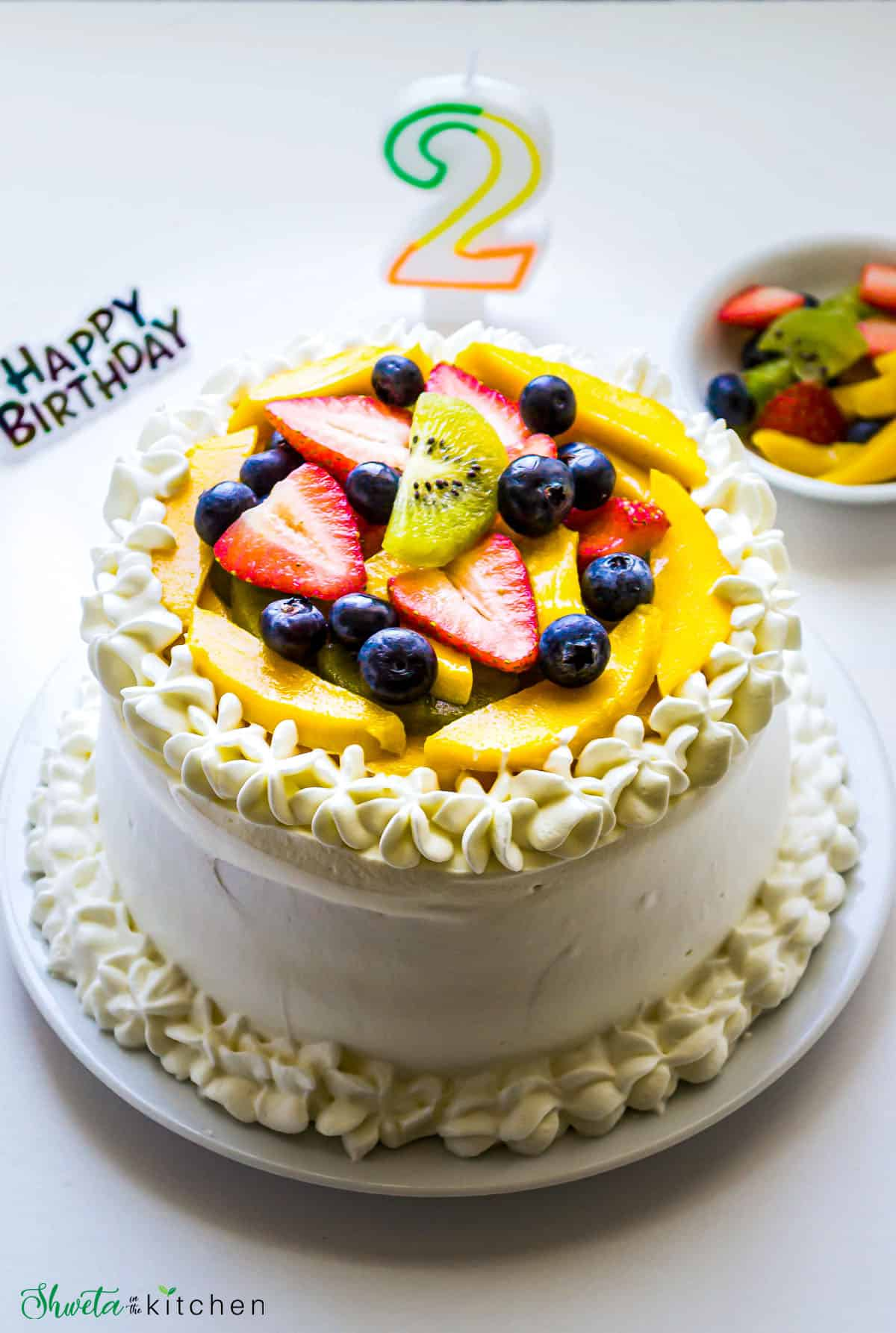 Layered  Vanilla Cream Sponge Cake frosted with whipped crea and decorated with fruits and number 2 candle.