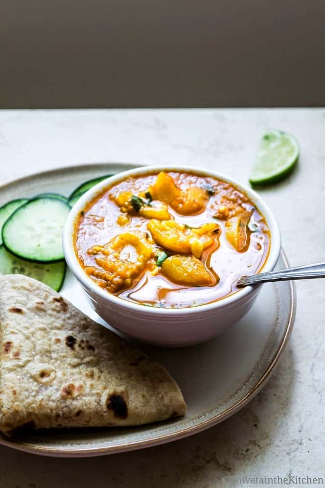 A spoon in a bowl of tinda curry served with roti and sliced cucumbers