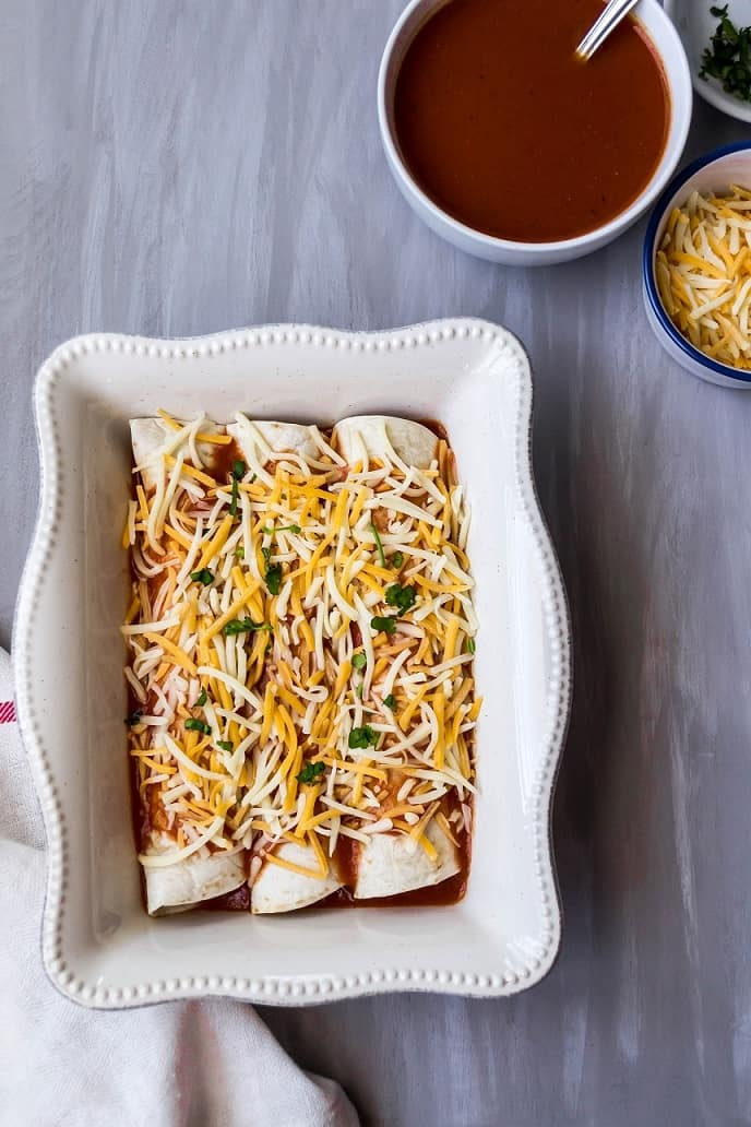 The enchiladas topped with shredded cheese before being baked