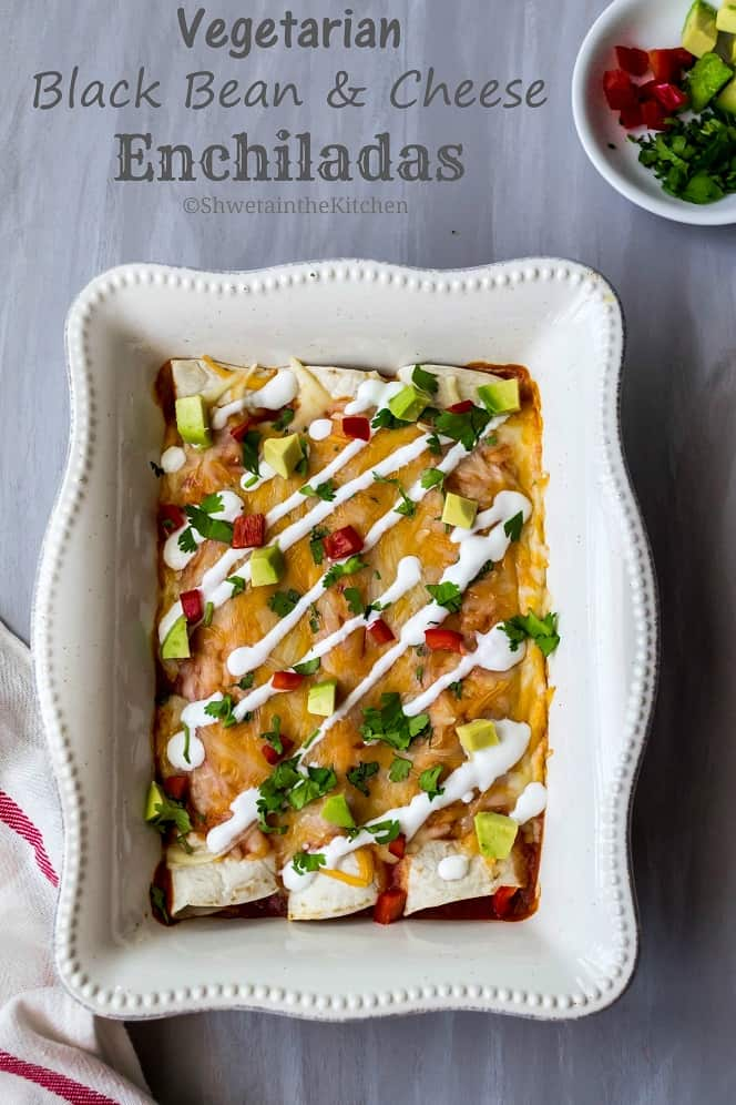 Vegetarian enchiladas in a white baking dish drizzled with sour cream