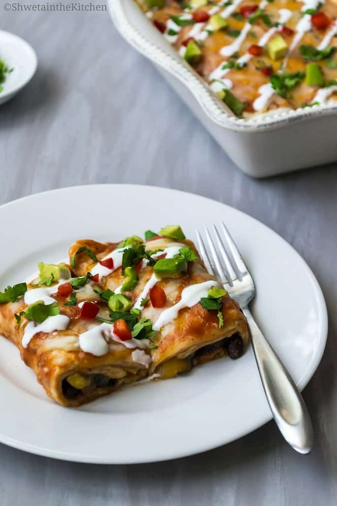 Veg Enchiladas served on a white plate with a fork. Topped with sour cream and fresh vegetables