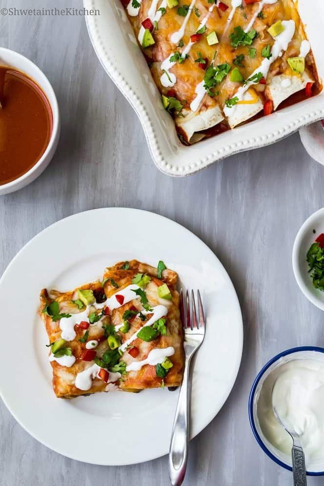 Overhead shot of vegetarian enchiladas served on a white plate next to bowls of toppings