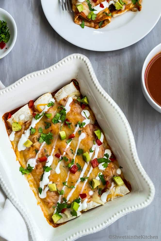 Black bean enchiladas topped with bell peppers, cilantro, avocado and sour cream