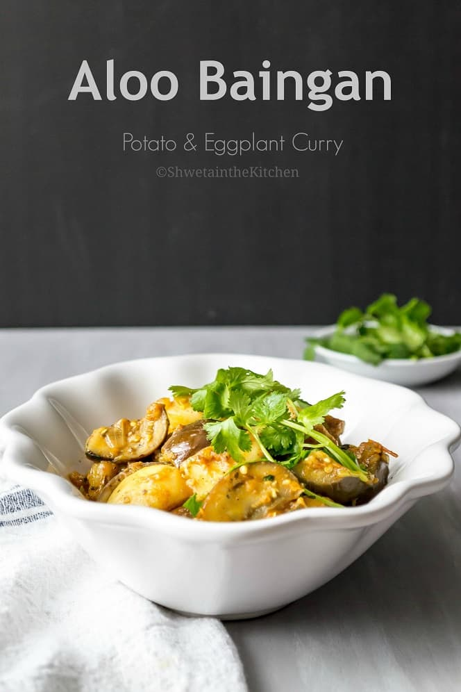 Close up of the potato and eggplant curry served in a white bowl and garnished with fresh herbs