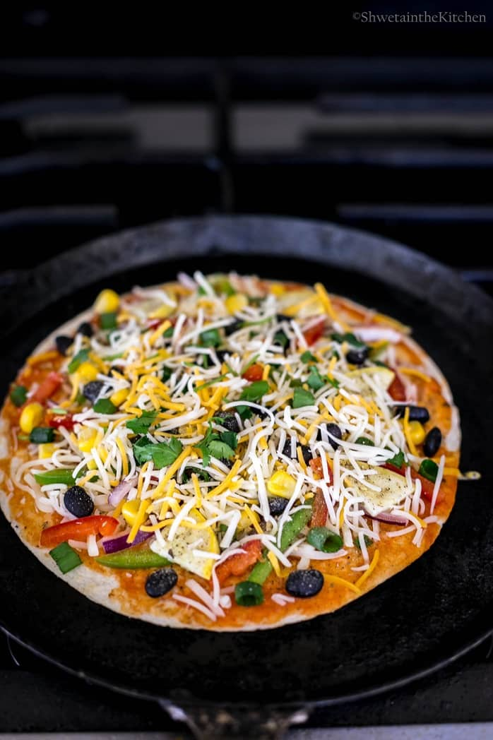 The tortilla pizza cooking on the stove top