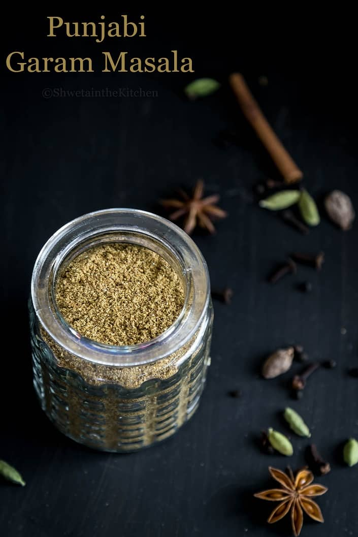 Punjabi garam masala in a glass jar surrounded by whole spices