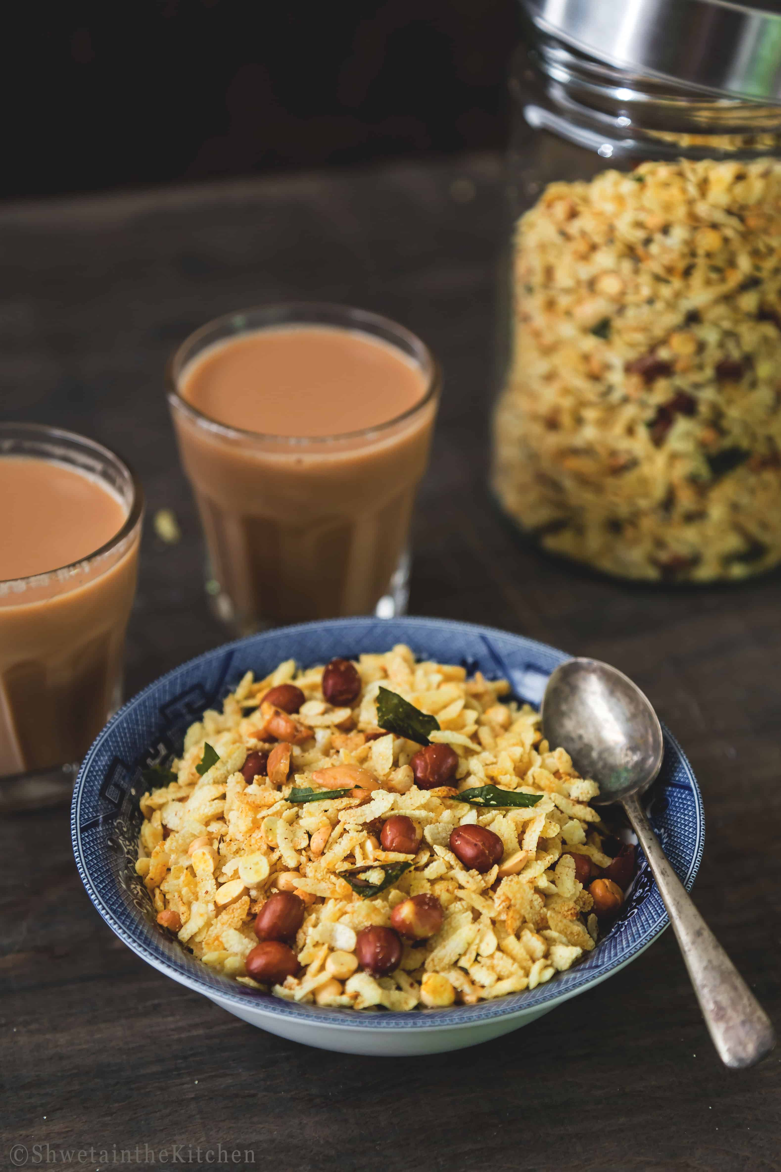 Poha Chivda in a bowl with spoon and 2 cups of chai