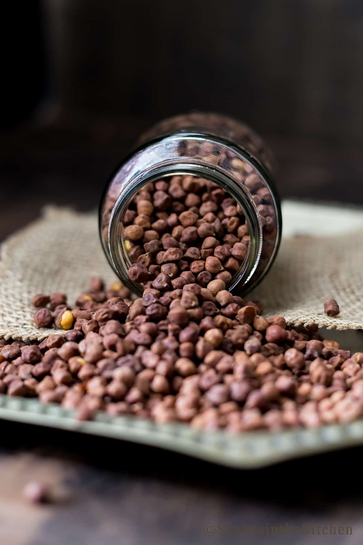 Dry black chickpeas in a jar that has fallen and the beans spilling out