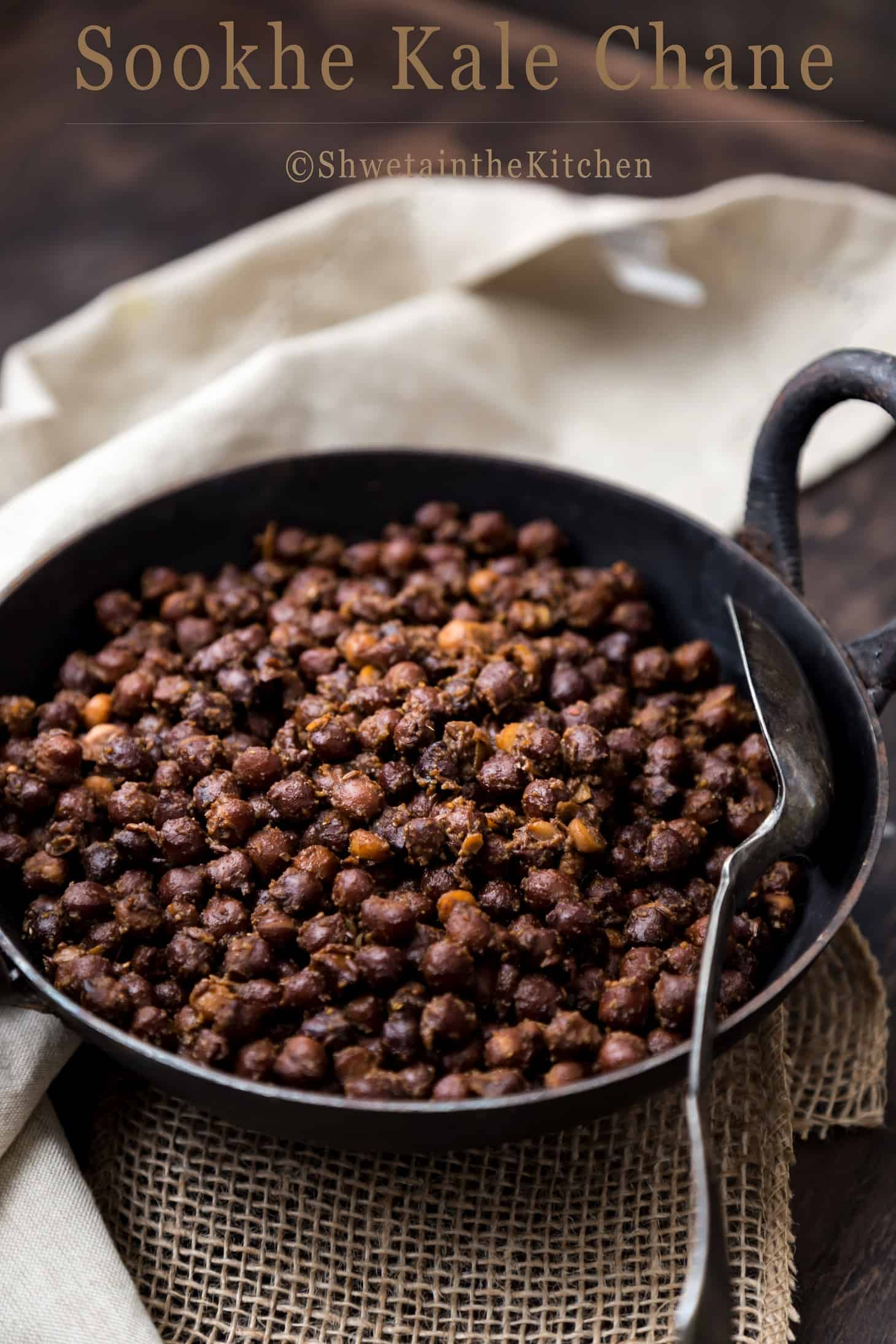 Sookhe Kala chana curry in black wok with spoon