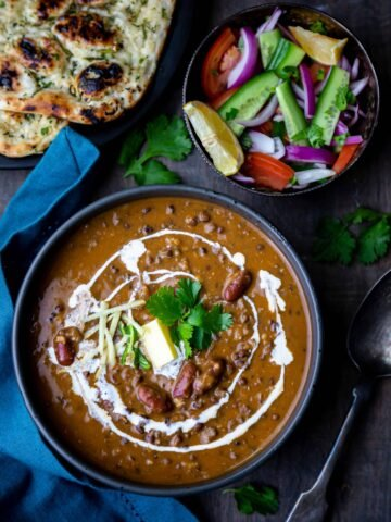 Punjabi Dal Makhani in a black bowl with salad bowl and naan on side