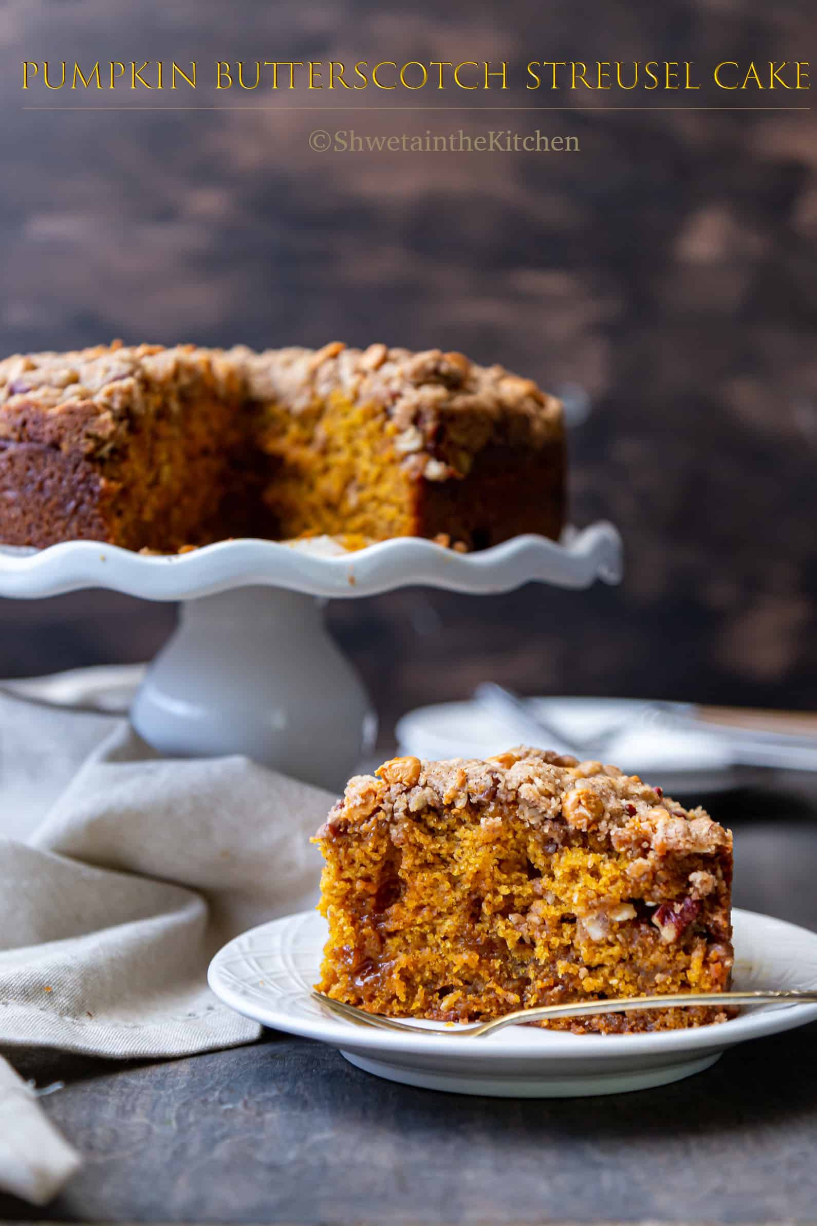 Pumpkin Streusel Cake slice in the front focus with cake in background on white stand.