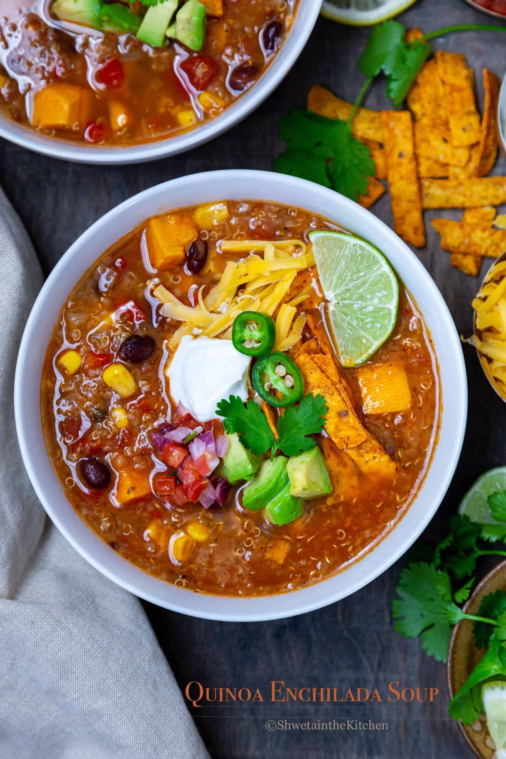 Quinoa Enchiladas Soup in bowl with toppings, cheese and lime.