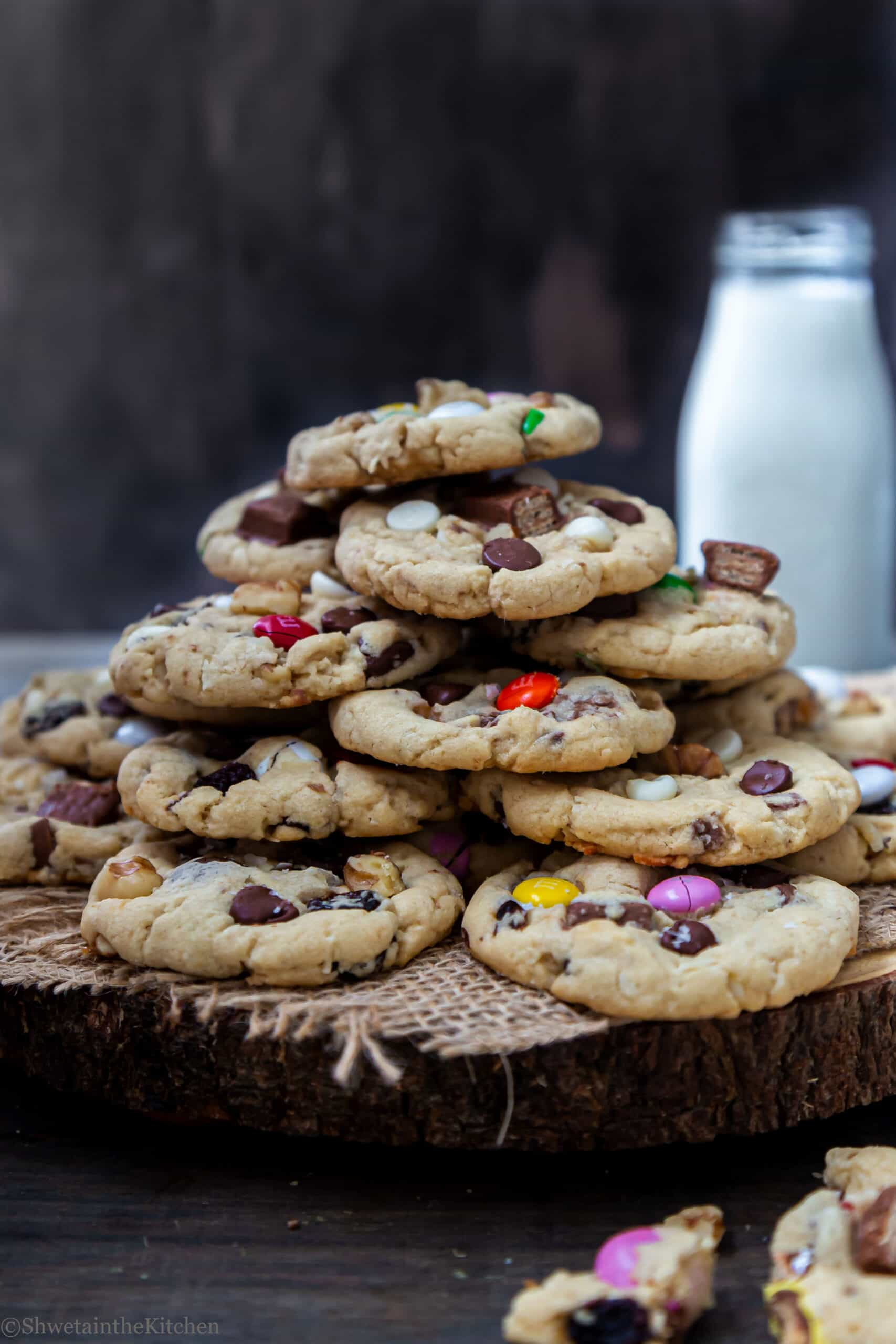 Heaped tower of Eggless Kitchen Sink Cookies on board with a bottle of milk in background