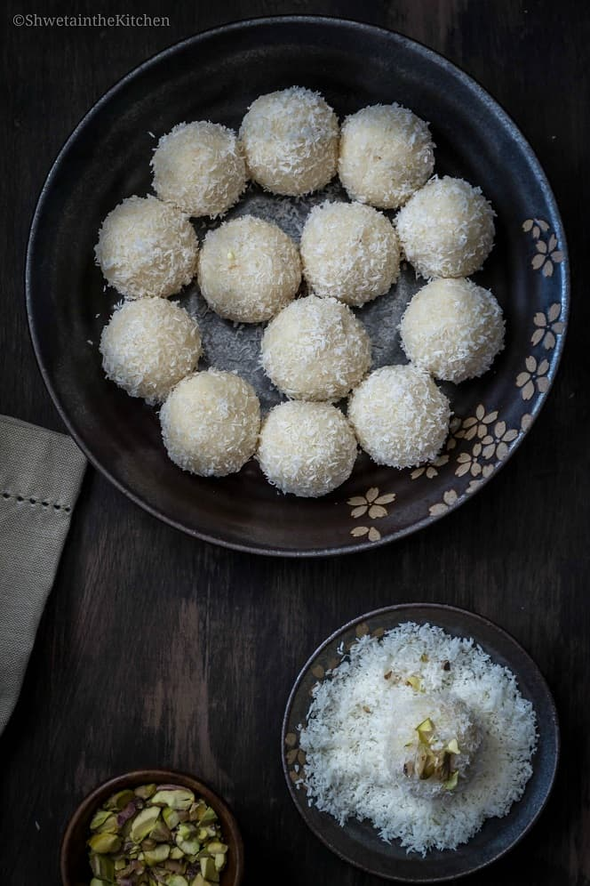Top view of Coconut Ladoo on a plate with one of the side dipped in desiccated coconut.