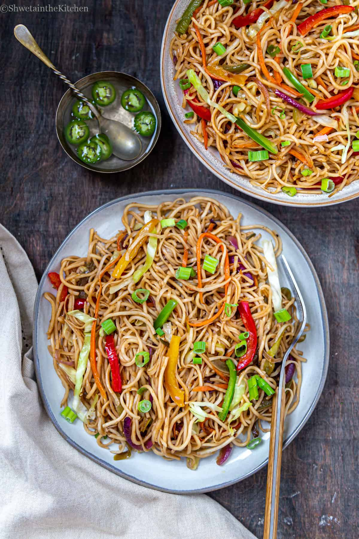 Top view of plate full of Indo chinese noodles with fork, bowl full of noodles and small bowl of vinegar and green chillies