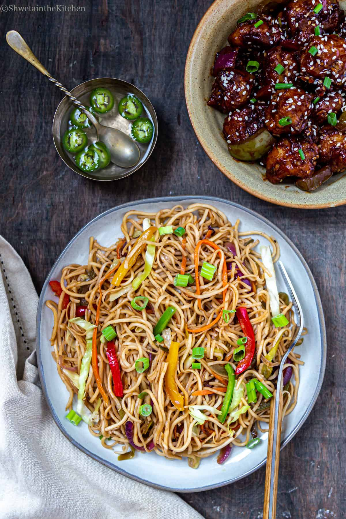 Top view of Hakka noodles on plate, bowl of gobi manchurian and bowl of vinegar with green chillies