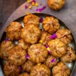 Fried Modak's arranged in tower on a plate, one placed on side with lamp light