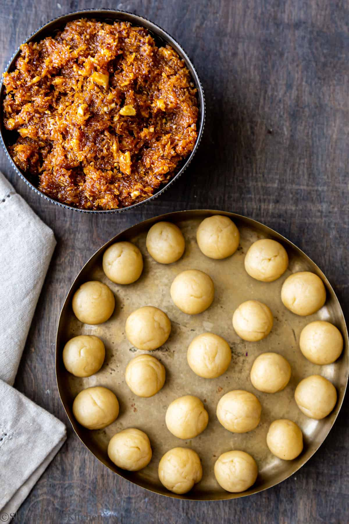 Bowl full of coconut, jaggery filling  and plate with round shaped dough balls.