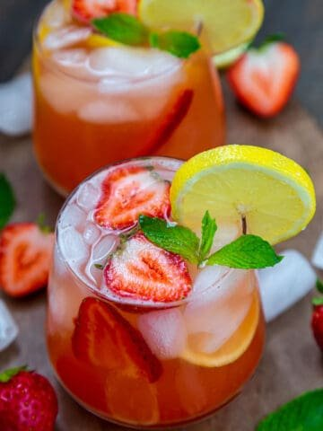 Two glasses of strawberry lemonade garnished with mint, a lemon slice and a fresh strawberry