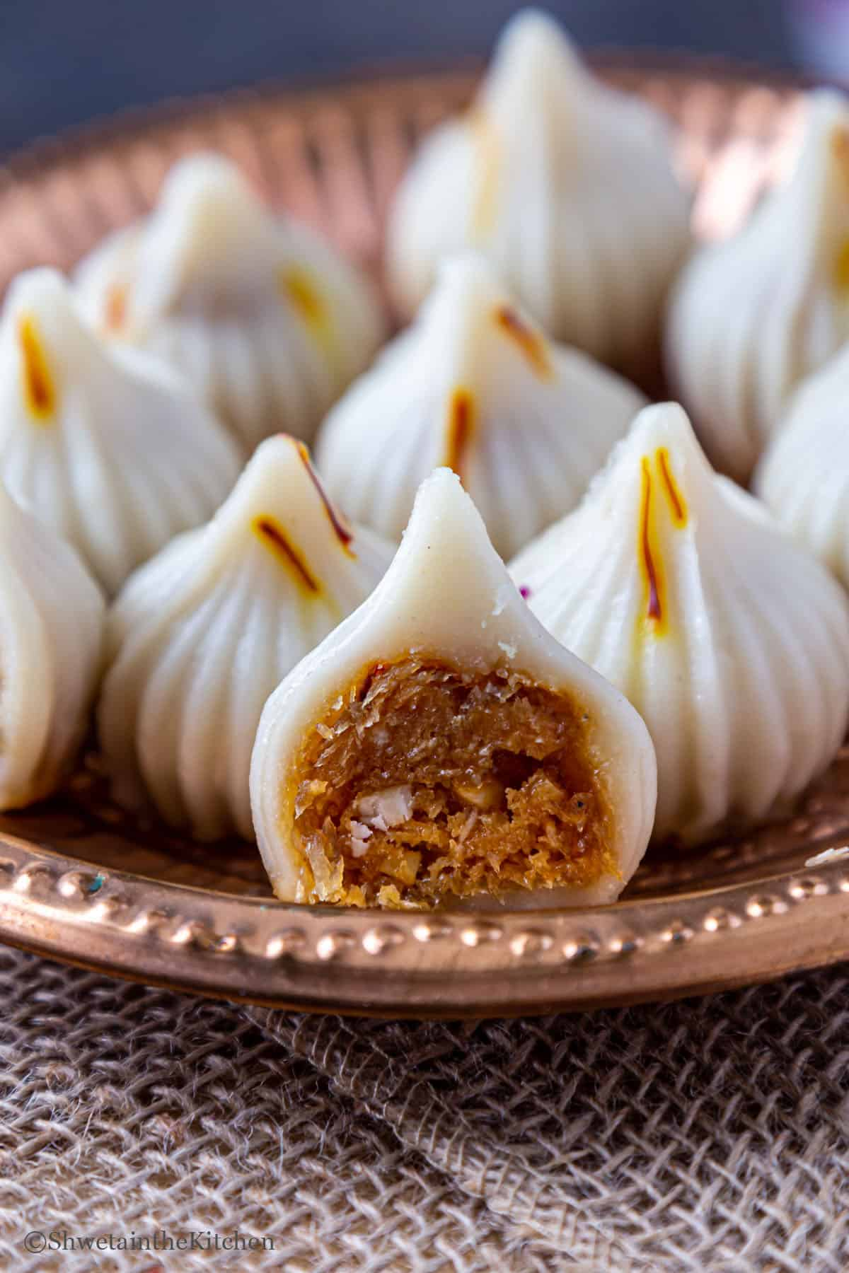 Modak halved to show filling inside and placed on plate full of modak