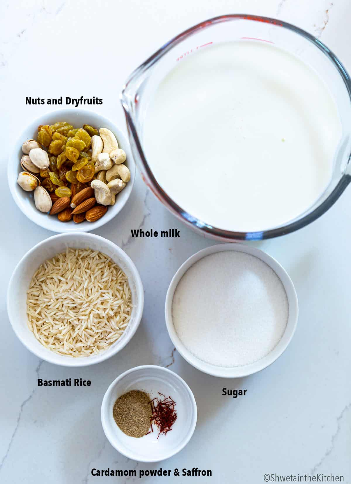 Ingredients for rice kheer arranged in white bowls and milk in glass jar