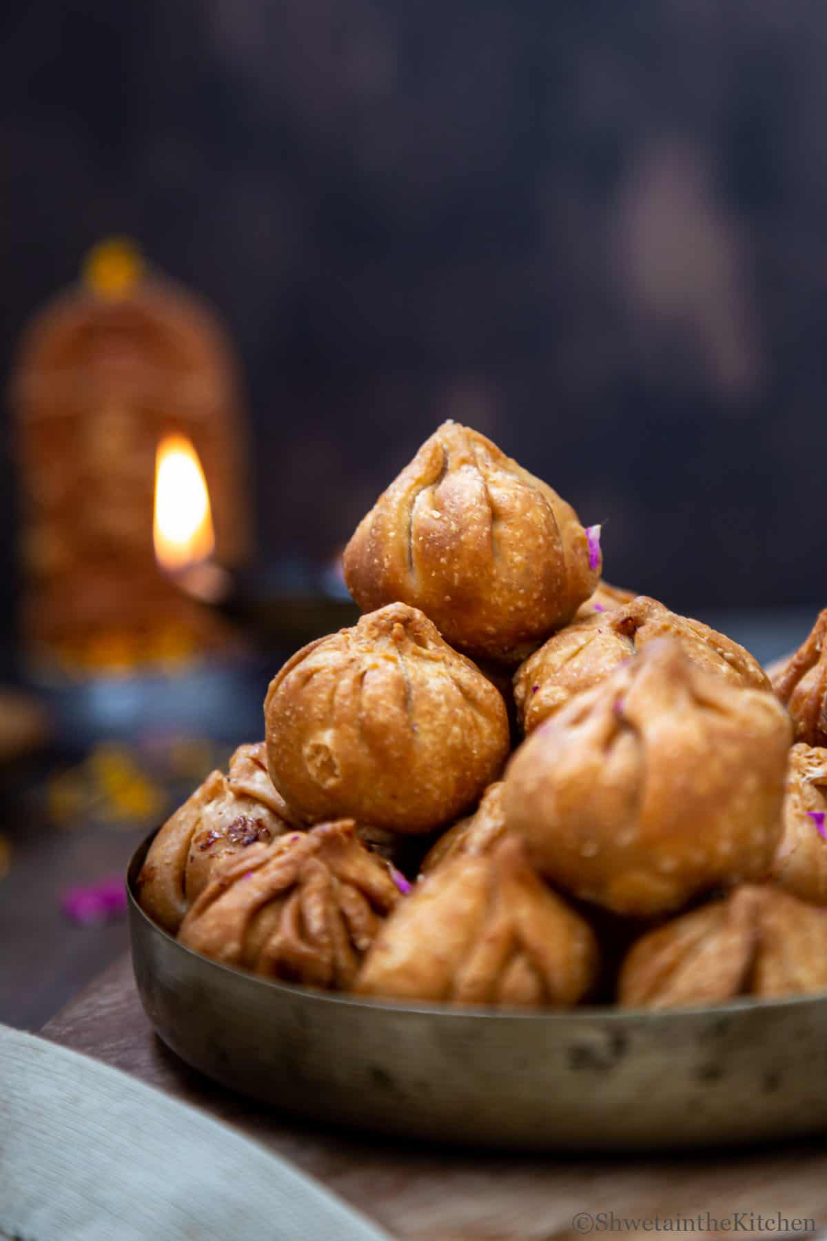 Fried Modak tower in focus with Lord Ganesha and light in background