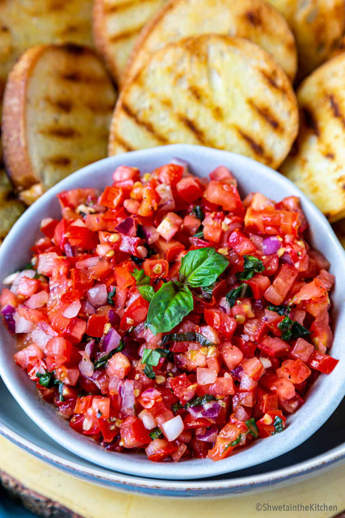Bowl of tomato bruschetta mixture with grilled bread on side