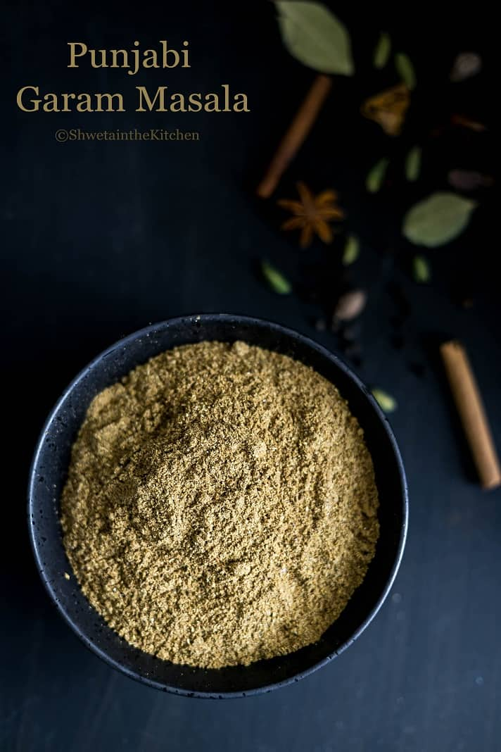 Garam masala in a black bowl next to whole spices
